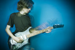 Eje de balancín que toca la guitarra en azul Foto de archivo libre de regalías