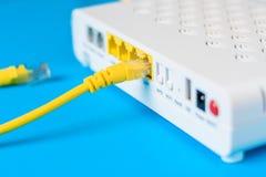 Eje del router del módem de Internet con un cable que conecta en fondo azul imágenes de archivo libres de regalías