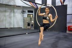 Ejecución acrobática joven de la mujer en aro aéreo Fotografía de archivo libre de regalías