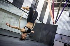 Ejecución acrobática joven de la mujer en aro aéreo Foto de archivo