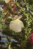 Ejecución amarilla de la bola de cristal en rama de árbol de navidad verde Fotografía de archivo