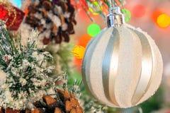 Ejecución brillante blanca de la bola en una rama nevada de un árbol de navidad contra un contexto de luces multicoloras Imagen de archivo
