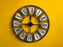 Ejecución clásica del reloj de pared en la pared amarilla Foto de archivo