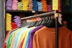 Ejecución colorida de la tela de las camisas de la tienda en un estante Foto de archivo