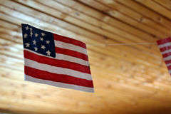Ejecución de la bandera americana en los hilos contra la perspectiva del techo de madera Imagen de archivo