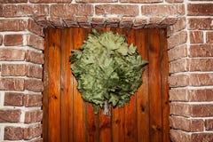 Ejecución de la escoba del baño en la puerta en la sauna Imagen de archivo libre de regalías