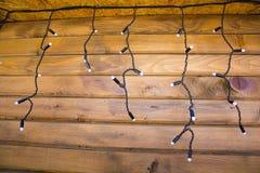 Ejecución de la guirnalda de la Navidad en la pared de madera Fotos de archivo libres de regalías