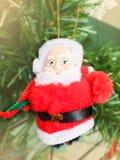 Ejecución de la muñeca de Papá Noel en el árbol de navidad imagen de archivo libre de regalías