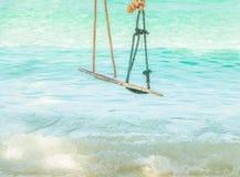 Ejecución de madera del oscilación en una rama del árbol en el mar de la turquesa Foto de archivo libre de regalías
