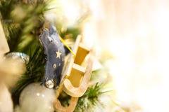 Ejecución de madera del trineo del juguete de la Navidad vieja en las velas ardientes de la rama, cajas, bolas, conos del pino, n Imagen de archivo libre de regalías