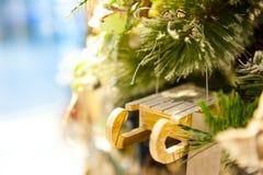 Ejecución de madera del trineo del juguete de la Navidad vieja en las velas ardientes de la rama, cajas, bolas, conos del pino, n Fotografía de archivo libre de regalías