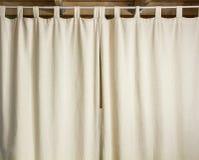 Ejecución de marfil de la cortina en una barra de metal imagen de archivo