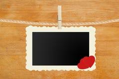 Ejecución de papel de la foto con dos corazones rojos en cuerda en de madera Foto de archivo libre de regalías