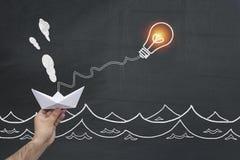 Ejecución de papel del barco en la bombilla Oportunidades de la ventaja del negocio y concepto del éxito dirección, independencia foto de archivo libre de regalías