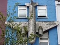 Ejecución del aeroplano en una pared azul Foto de archivo libre de regalías