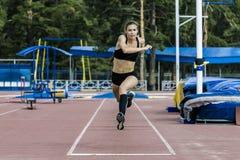 Ejecución del atleta de la muchacha de la triple salto Imágenes de archivo libres de regalías