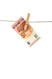 Ejecución del billete de banco del euro 10 en cuerda para tender la ropa en el fondo blanco Foto de archivo