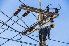 Ejecución del electricista en el polo de la electricidad Foto de archivo libre de regalías