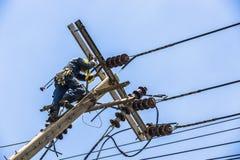 Ejecución del electricista en el polo de la electricidad Imágenes de archivo libres de regalías