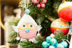 Ejecución del juguete de la Navidad en las velas ardientes de la rama, cajas, bolas, conos del pino, nueces, Branchesin el fondo  Foto de archivo