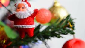 Ejecución del juguete de Santa Claus en un árbol de abeto con la iluminación de destello en fondo almacen de metraje de vídeo