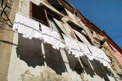 Ejecución del lavadero en una línea de ropa en un edificio viejo de la ciudad Lavadero y paredes de la ejecución Foto de archivo