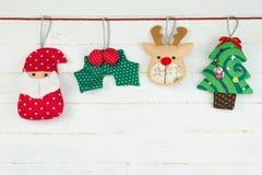 Ejecución del ornamento de la muñeca de la Navidad con la cuerda en el backgro de madera blanco Imagen de archivo libre de regalías