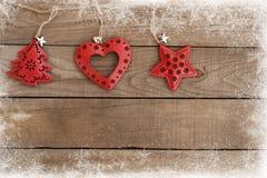 Ejecución del ornamento de Navidad en el fondo de madera de la pared Imagenes de archivo