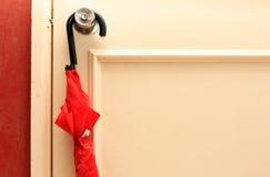 Ejecución del paraguas en botón de puerta Aliste para ser cogido durante la lluvia Fotografía de archivo