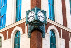 Ejecución del reloj de la calle del vintage en una esquina del edificio de ladrillo Fotos de archivo libres de regalías