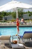 Ejecución del sujetador en un paraguas cerca de la piscina fotos de archivo