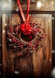 Ejecución hecha a mano de la guirnalda de la Navidad en puerta de madera vieja envejecida con la cinta roja y bayas con nieve Fotografía de archivo libre de regalías