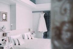 Ejecución nupcial elegante blanca del vestido en una suspensión de madera en la habitación de lujo en estilo minimalista Fotos de archivo libres de regalías