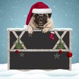 Ejecución preciosa del perro de perrito del barro amasado de la Navidad con las patas en muestra en blanco de la pizarra con el m imagen de archivo libre de regalías