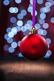 Ejecución roja de la bola de la Navidad en una cinta rosada en una tabla de madera fotografía de archivo libre de regalías