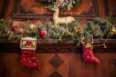 Ejecución roja del calcetín de la Navidad en la chimenea Ramas Spruce, humor de la Navidad de los juguetes imagen de archivo