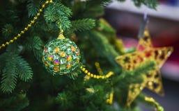 Ejecución verde en un árbol de navidad, bola moderna de la bola de la Navidad adornada con los cristales Imagen de archivo libre de regalías