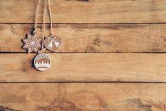 Ejecución de la decoración de la Navidad en la textura de madera del fondo con el poli Fotos de archivo