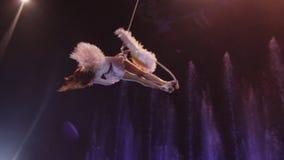 Ejecutante aéreo que hace el acto acrobático contra las fuentes coloridas, la acrobacia, Moscú, Rusia almacen de metraje de vídeo