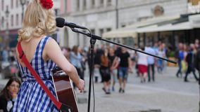 Ejecutante de la calle que toca la guitarra y que canta en el micrófono