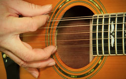Ejecutante que juega en la guitarra acústica Fotos de archivo
