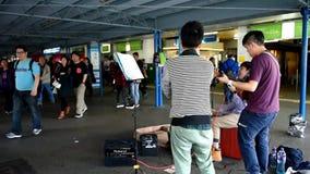 Ejecutantes de la calle en Tsim Sha Tsui Star Ferry Pier en Hong Kong almacen de metraje de vídeo