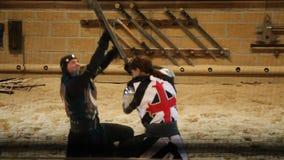 Ejecutantes en batalla medieval del traje durante el torneo metrajes