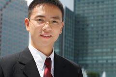 Ejecutivo asiático joven delante de los edificios de oficinas Imagen de archivo libre de regalías