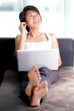 Ejecutivo asiático joven que se relaja en el sofá que escucha imagen de archivo