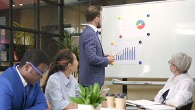 Ejecutivo confiado de sexo masculino que presenta meta financiera en el informe en oficina metrajes