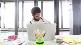 Ejecutivo creativo de sexo masculino que habla en el teléfono mientras que trabaja en el ordenador portátil almacen de metraje de vídeo