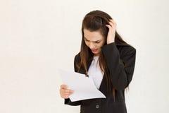 Ejecutivo de operaciones de sexo femenino infeliz que mira el documento o el informe Fotos de archivo