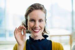 Ejecutivo de operaciones de sexo femenino sonriente con las auriculares que se sientan en oficina Imagenes de archivo