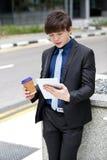 Ejecutivo de operaciones de sexo masculino asiático joven que usa la tableta Imagenes de archivo